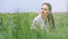Young relaxing woman sitting in the grass Royalty Free Stock Photo