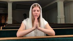 Young religious devoted woman praying in baptist church. Faithful catholic at european cathedral: inside of holy place.  stock footage