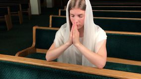 Young religious devoted woman praying in baptist church. Faithful catholic at european cathedral: inside of holy place.  stock video footage