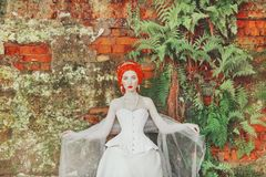 Young renaissance redhead countess with hairstyle in the old castle. Fabulous rococo queen in white dress against the backdrop of. Old stone wall. Doll in the stock photography
