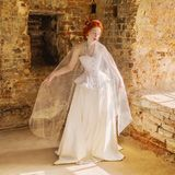 Young renaissance redhead princess with hairstyle in old castle from fairytale. Doll in corset. Renaissance princess in palace. Fairytale queen in white dress stock image