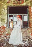 Young renaissance redhead princess in old castle. Fabulous rococo queen in white dress against backdrop of old stone wall. Doll in the corset. Victorian stock image