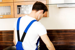Young repair man measuring kitchen cabinet Stock Images