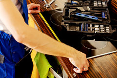 Young repair man measuring kitchen cabinet Royalty Free Stock Images