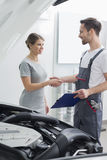 Young repair worker shaking hands with customer in car workshop Stock Photography
