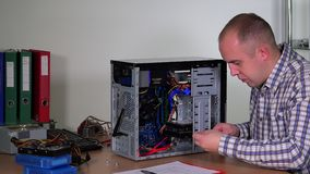 Young repairer man installing hard drive into desktop pc case at computer center stock video footage