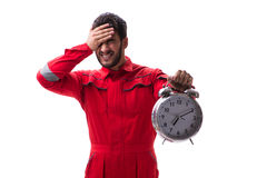 The young repairman with an alarm clock isolated on white background Royalty Free Stock Image