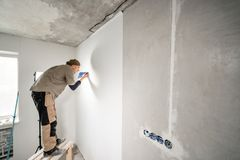 Young repairman aligns with plastic spatula. Worker glueing wallpapers on concrete wall. Repair the apartment. Home. Young man, worker glueing wallpapers on royalty free stock photo