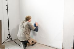 Young repairman aligns with plastic spatula. Worker glueing wallpapers on concrete wall. Repair the apartment. Home. Young man, worker glueing wallpapers on stock photo