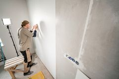 Young repairman aligns with plastic spatula. Worker glueing wallpapers on concrete wall. Repair the apartment. Home. Young man, worker glueing wallpapers on stock images