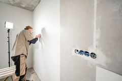Young repairman aligns with plastic spatula. Worker glueing wallpapers on concrete wall. Repair the apartment. Home stock photo