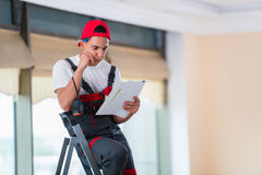 The young repairman checking the drawings before starting the work Royalty Free Stock Photo