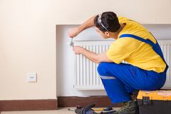The young repairman contractor repairing heating panel. Young repairman contractor repairing heating panel Stock Image