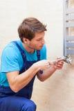 Young repairman fixing heater Royalty Free Stock Photos