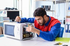 The young repairman fixing and repairing microwave oven. Young repairman fixing and repairing microwave oven Royalty Free Stock Photo