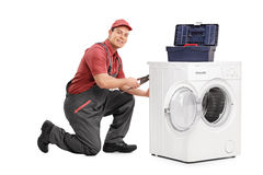 Young repairman fixing a washing machine. And looking at the camera isolated on white background Stock Image