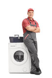 Young repairman leaning on a washing machine Royalty Free Stock Photography