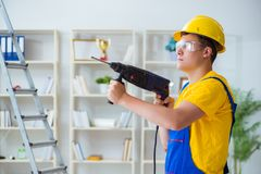 The young repairman with power drill. Young repairman with power drill Royalty Free Stock Photos