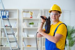 The young repairman with power drill. Young repairman with power drill Royalty Free Stock Images