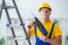 The young repairman with power drill. Young repairman with power drill Royalty Free Stock Photo