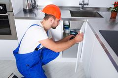 A young repairman is repairing a kitchen cabinet with a screwdriver royalty free stock images