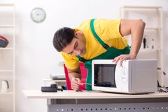 The young repairman repairing microwave in service centre royalty free stock photo