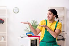 Young repairman repairing microwave in service centre stock photos