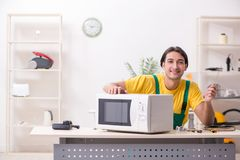 Young repairman repairing microwave in service centre royalty free stock images