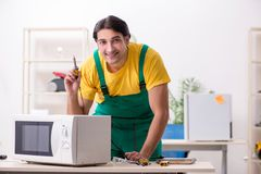 Young repairman repairing microwave in service centre royalty free stock photography