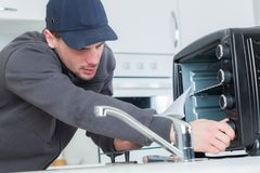 Young repairman repairing oven with screwdriver in clients kitchen. Technician royalty free stock photo