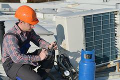 Air Conditioning Repair. Young repairman on the roof fixing air conditioning system Royalty Free Stock Photo