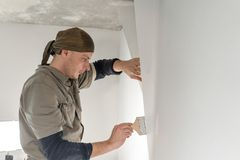 Young repairman smear on wall glue with a brush. Worker glueing wallpapers on concrete wall. Repair the apartment. Home. Young man, worker glueing wallpapers on royalty free stock image