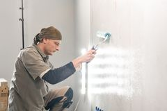 Young repairman smear on wall glue with a roller. . Worker glueing wallpapers on concrete wall. Repair the apartment. Young man, worker glueing wallpapers on stock photo
