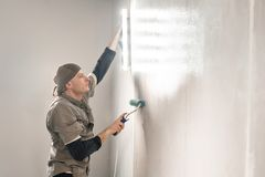 Young repairman smear on wall glue with a roller. . Worker glueing wallpapers on concrete wall. Repair the apartment. Young man, worker glueing wallpapers on royalty free stock photos