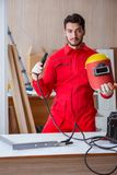 Young repairman with a welding gun electrode and a helmet weldin Royalty Free Stock Photos