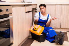 The young repairman working at the kitchen Stock Images