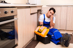 The young repairman working at the kitchen Stock Image