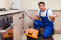 The young repairman working at the kitchen Royalty Free Stock Photography