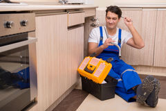 The young repairman working at the kitchen Royalty Free Stock Images
