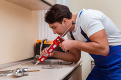 The young repairman working at the kitchen. Young repairman working at the kitchen Royalty Free Stock Images