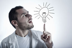Young researcher with an idea. A young researcher/doctor in a lab coat having an idea (light bulb draw Royalty Free Stock Photos