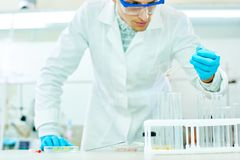 Young Researcher with Test Tube. Handsome young researcher wearing safety goggles and white coat looking at test tube with concentration while carrying out Stock Photography