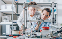 Young researchers and 3D printer. Young students researchers using an innovative 3D printer in the laboratory, engineering and prototyping concept royalty free stock photo