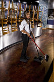 Young restaurant worker sweeping floor. Young Hispanic female worker sweeping floor of closed restaurant Royalty Free Stock Images