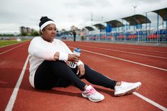 After exercising. Young restful woman sitting on race track and refreshing with water after training Stock Photos