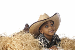 Young Resting Cowboy. An African cowboy happily resting in the hay cowboy boots and an oversized hat. On a white background royalty free stock image