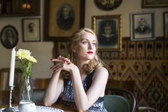 Young retro woman sitting at a table. Stock Image
