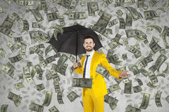 Young rich businessman standing in money rain. Umbrella above head Royalty Free Stock Photo