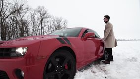 Young rich businessman walking on snowy field to red muscle car. Young rich caucasian businessman in brown coat walking on snowy field to red muscle car, cloudy stock video footage
