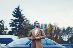 Young rich man. In a coat against the background of the car stock images